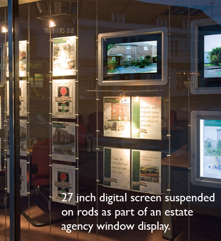 An estate agents window with a 27 inch digital screen suspended on rods as part of the displyay