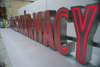 Internally illuminated brushed stainless steel built up letters with red acrylic mimicking neon style.