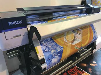 The SureColor SC S60600 printer printing a orange juice bottle