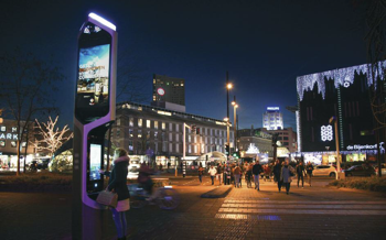 A streetview in a city at night with a smart kiosk
