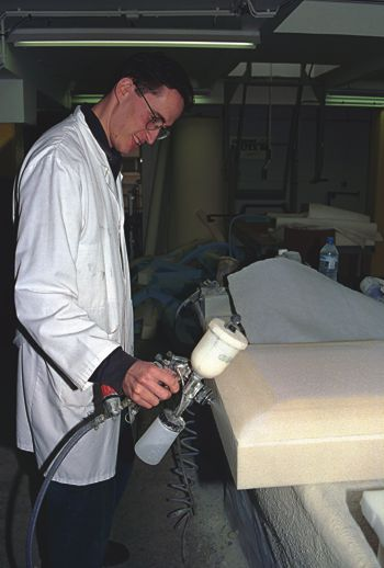 Man spraying water based adhesives.