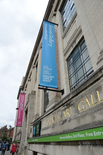 Promotional banner hanging from the side of an art gallery