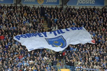 Pompey flag being held by football fans in a crowd at a match.