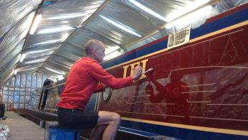 Man signwriting a canal boat by hand
