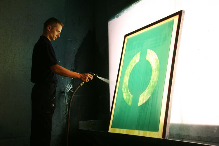 Man hosing down a screen from the screen printing methods used as part of the production