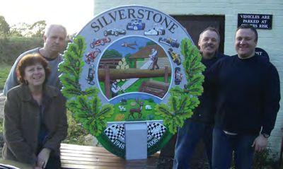 The finished village sign with workers from Rock Artisan Foundry