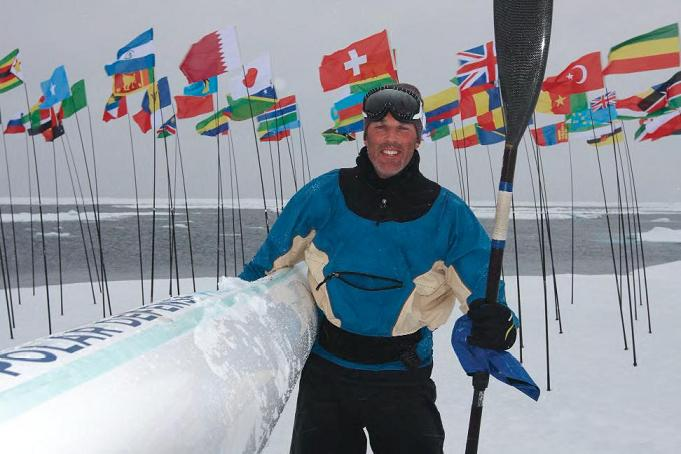 Lewis standing on Arctic ice with his kayak in front of 192 flags