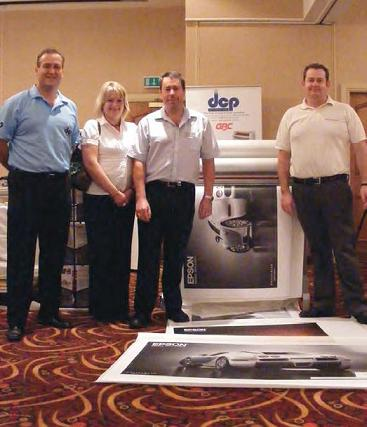 People from DCP Systems and the University Print Service in front of the laminator and some prints.