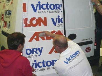 Van being wrapped in Victory Design's Logo.