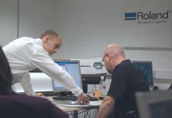 The trainer demonstrating to a peson at a computer at Walsall College.