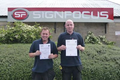 Paul Pratchett and Sam Johnson standing in front of SignFocus premises with their certificate