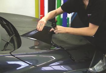 person removing film from car using IP vinyl remover
