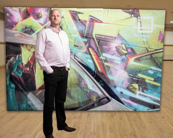 Paul Tomlinson in front of a fabric display