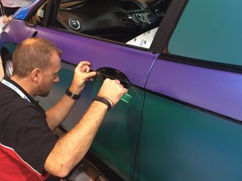 man wrapping a car with vinyl