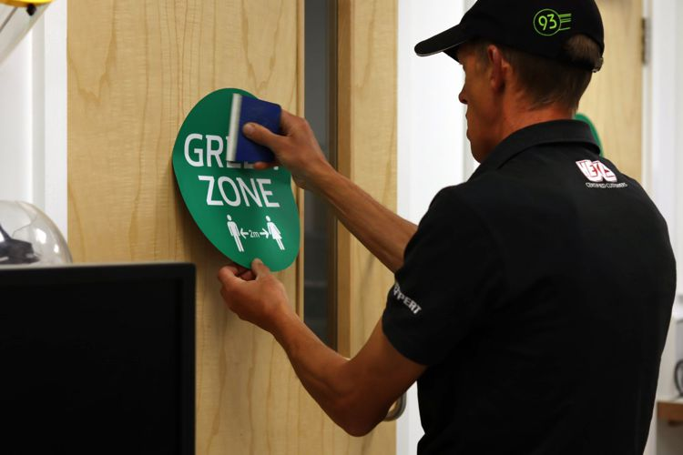 Green zone sticker being put on a door