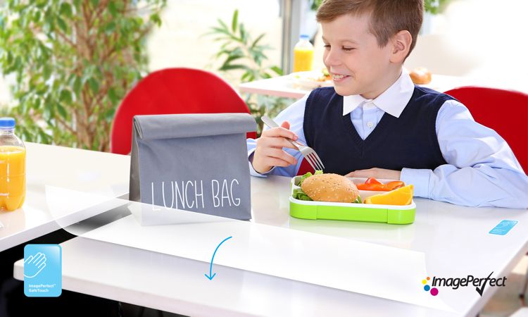 A boy eating lunch at a table covered by ImagePerfect's Safetouch
