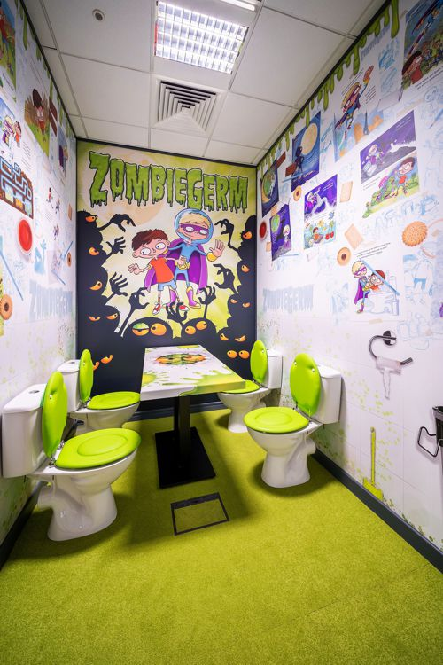 A very colourful room using toilets as seats, and with graphics on all the walls.