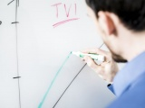 Man drawing a graph on a white board