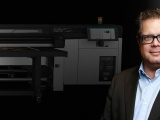 Terry Raghunath from HP, with a wide format printer in the background.