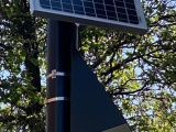 A solar panel and loudspeaker on a lamppost