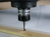 The Amana '0' series single flute tool cutting material on a CNC router